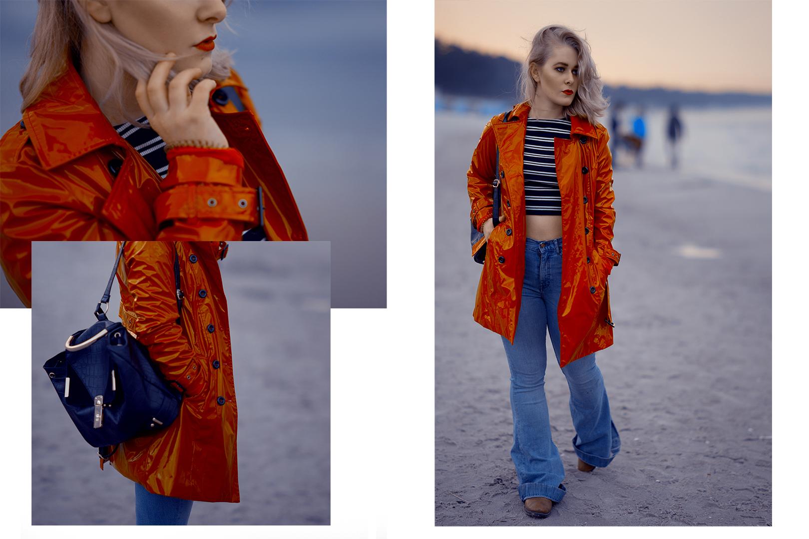 Blaue Jeans, schwarzer Rucksack und roter Lackmantel an der Ostsee