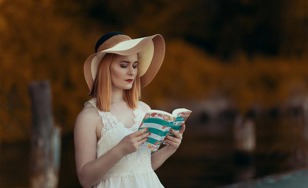 Spitzenkleid in weiß brauner Hut Buch Sommer Roman