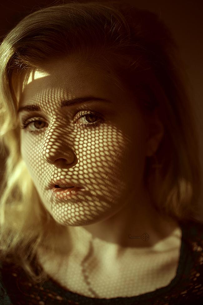 Portrait Frau mit Schattengitter auf Gesicht