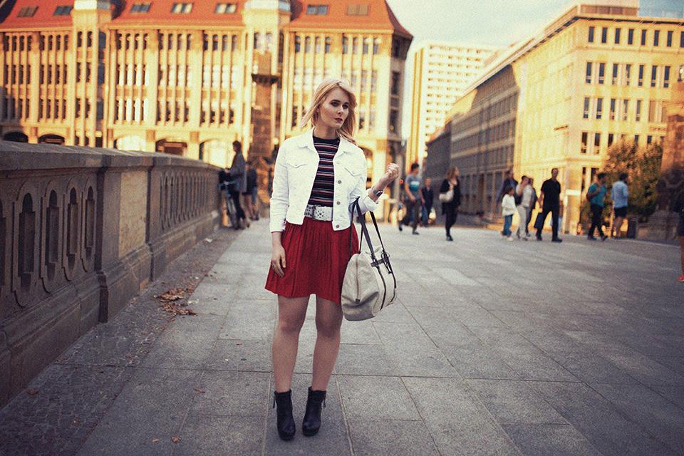 christina-key-traegt-einen-roten-plisseerock-und-eine-weisse-jackes