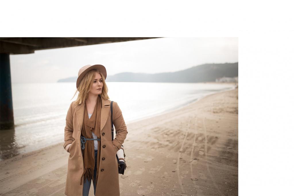 Christina Key trägt einen langen, braunen Mantel und eine braune Franzenweste im Boho Look