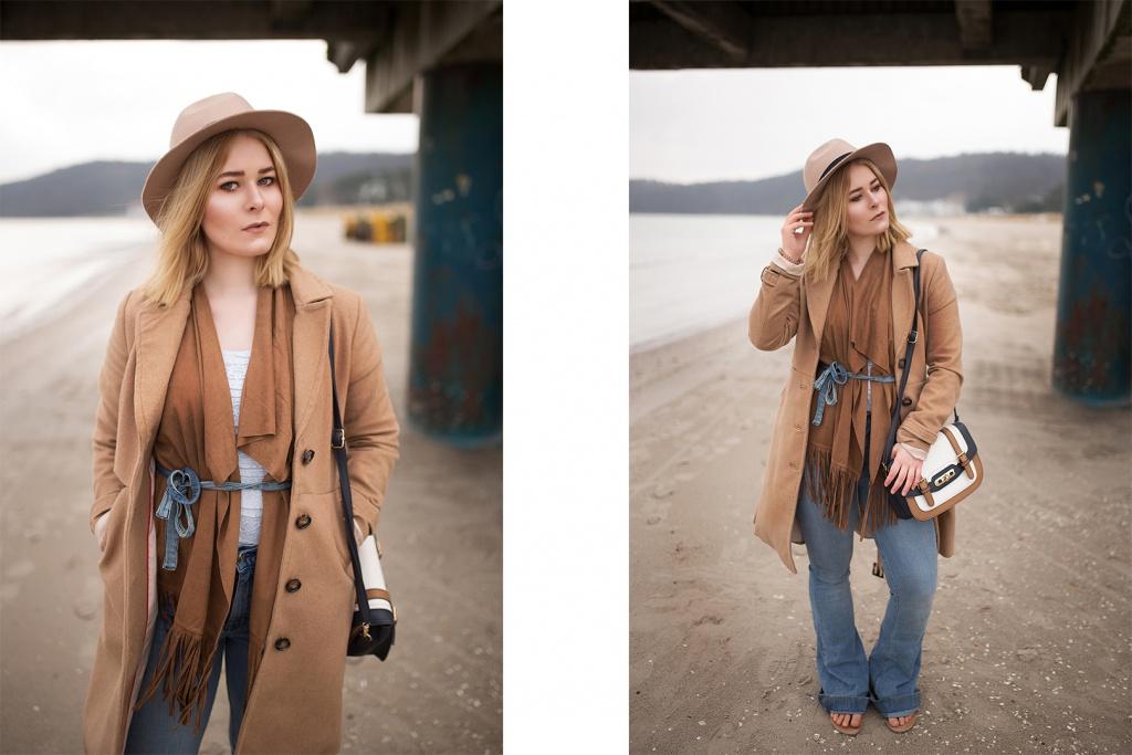 Fashion Bloggerin trägt einen camel farbenen Mantel, eine Franzen Weste und einen schicken Hut am Strand von Rügen
