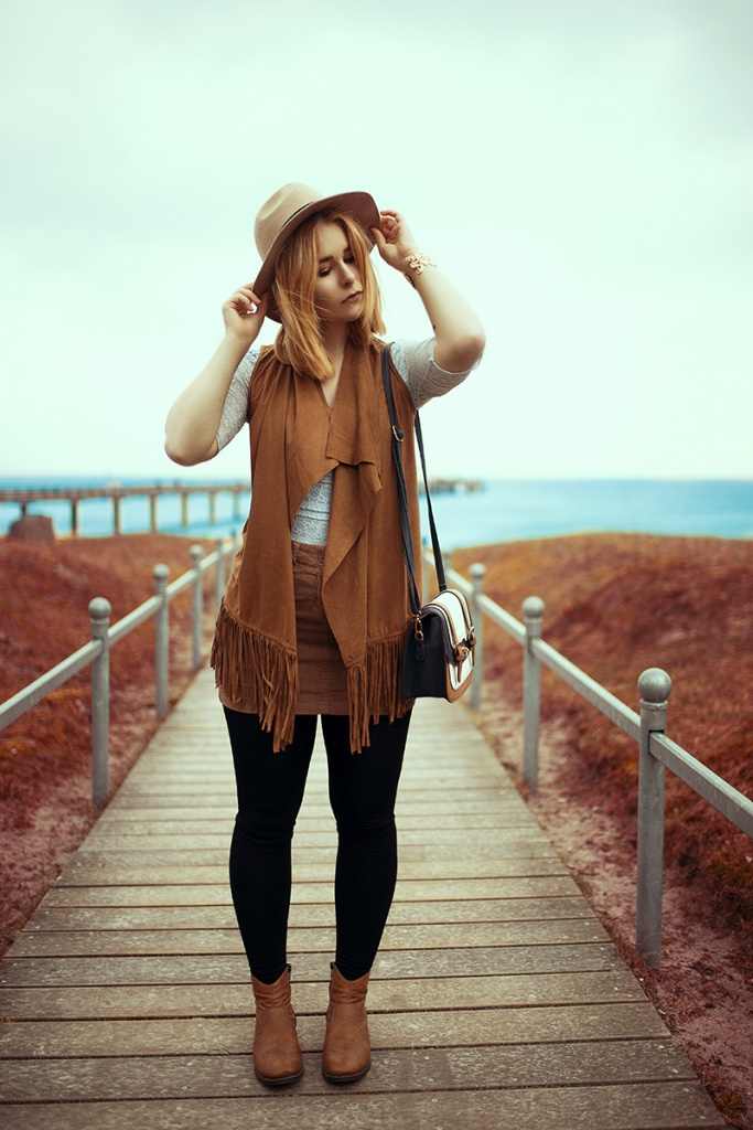 The blonde photographer Christina Key is wearing a brown cord skirt, a blue lace top and a beautiful boho jacket