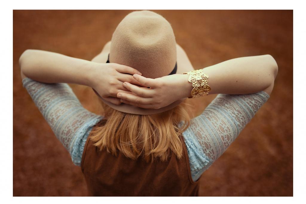 Blonde Haare treffen auf einen beige farbenen Hut und ein hellblaues Spitzenoberteil