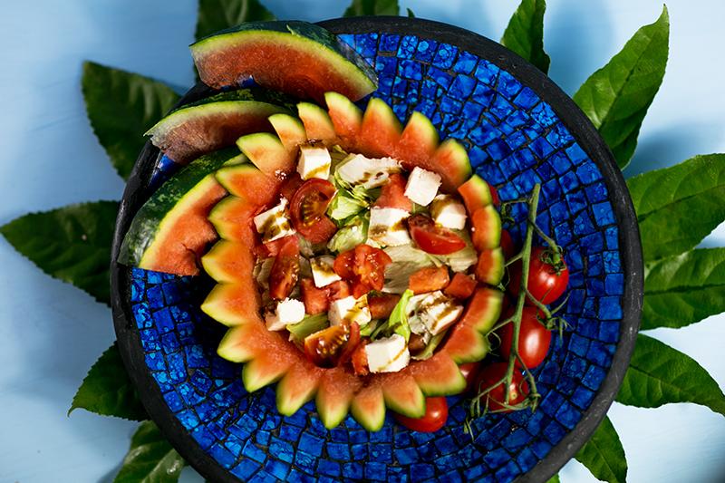 Erfrischender Sommer Salat mit Wassermelone, Feta und Tomaten in einer Wassermelone
