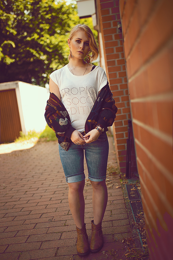 Bomberjacke weißes Top Jeans Hose und Boots Outfit