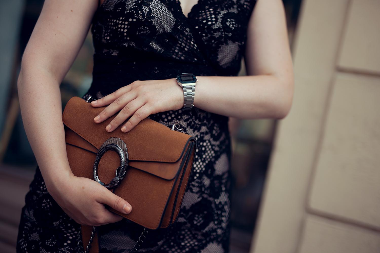 Schwarzes Kleid aus Spitze braune Tasche