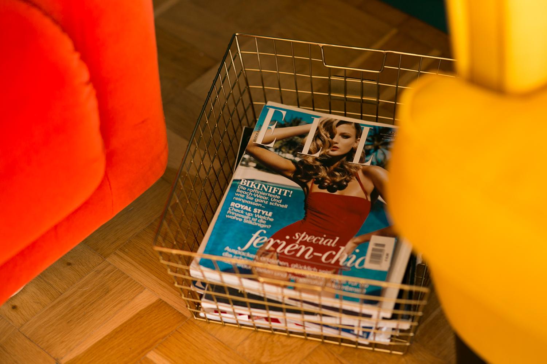 Zeitschriften in goldenem Drahtkorb