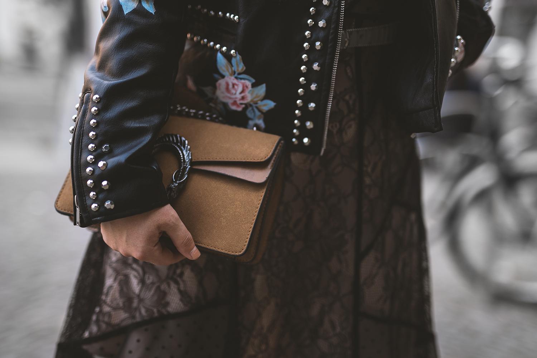 Schwarzes Spitzenkleid und Lederjacke