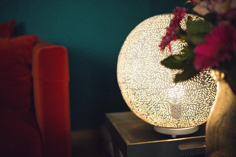 Weiße Tischleuchte in Kugelform Licht an